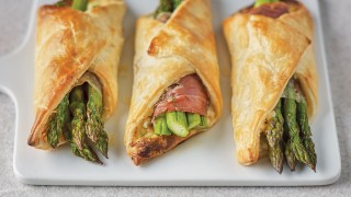 Three Asparagus and Parma Ham Pastries served on a white board