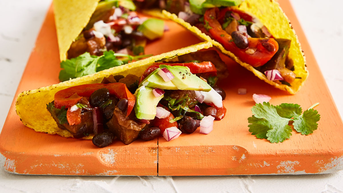 Aubergine Tacos served on a wooden board with avocado and red onion