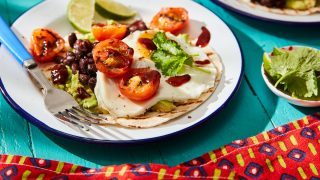 Avocado and Black Bean Breafast Tacos topped with coriander and lime wedges