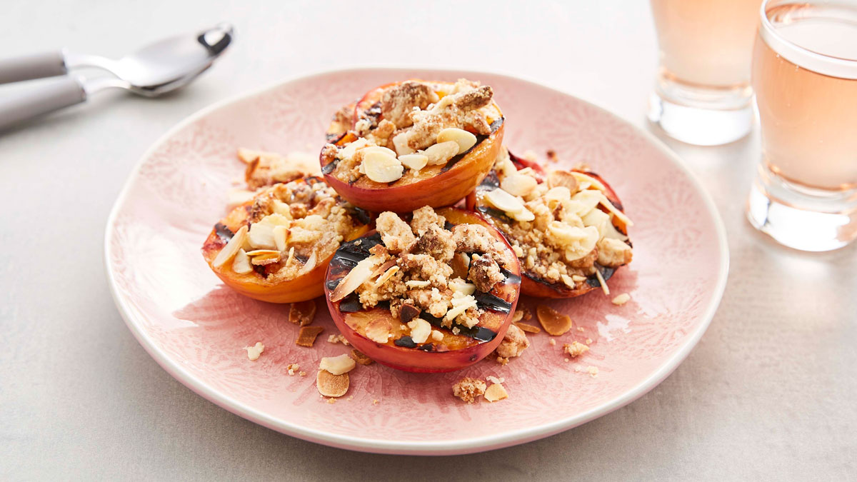 BBQ Grilled Peaches with Amaretti Crumble served on a pink plate