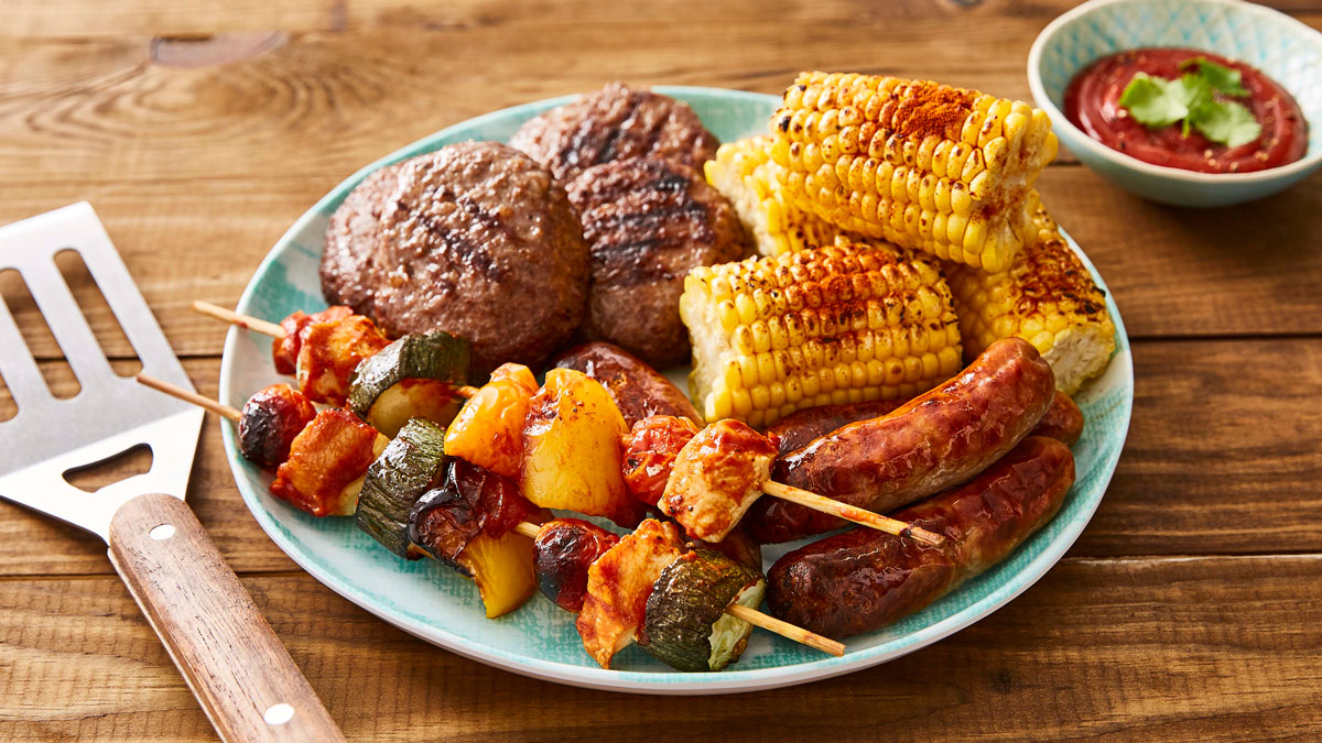 Plate of BBQ food including grilled corn, sausages, burgers and kebabs