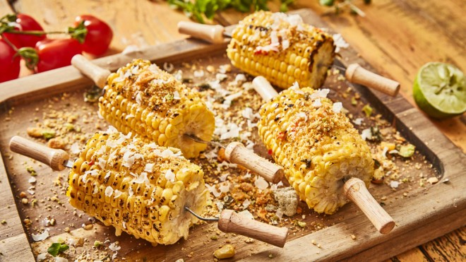 BBQ Sweetcorn with Chilli Butter, served on corn holders, on a wooden board