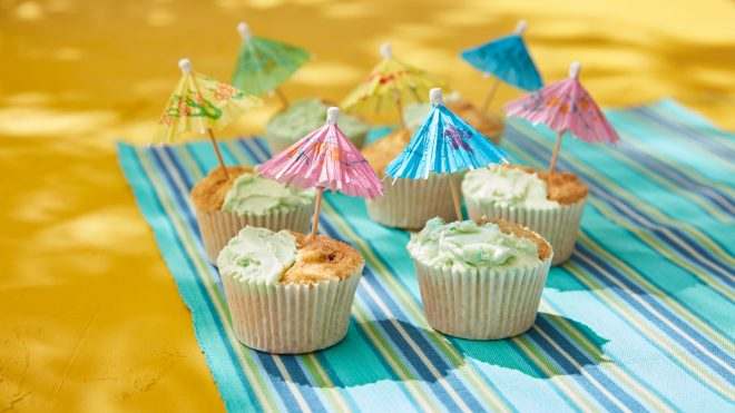 Beach Fun Cupcakes on a beack towel, with paper umbrellas in the top