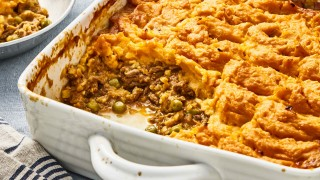 Spiced Beef and Lentil Bake with Sweet Potato Topping served in a white casserole dish with a portion removed to see the filling