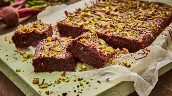 Beetroot Brownies topped with pitachios, served on baking parchment and sliced