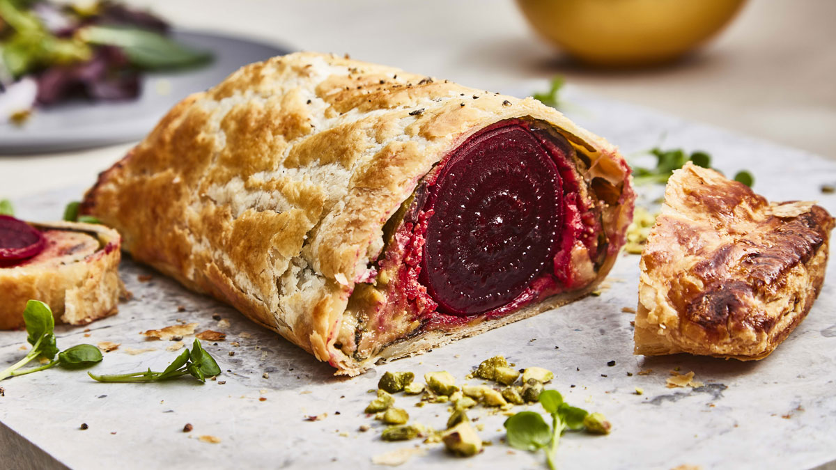 Beetroot Wellington served on a marble board, sliced to see the filling
