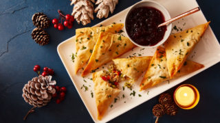 Festive Filo Parcels served on a white plate with a dish of cranberry sauce