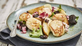 Warm Scallop, Black Pudding and Pear Salad served on a blue plate