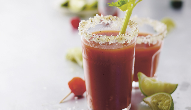 The Perfect Bloody Mary served in a glass, garnished with salt and pepper and a celery stick