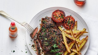 Bloody Mary Rump Steak served on a white plate with homemade chips, grilled tomatoes and topped with parsley
