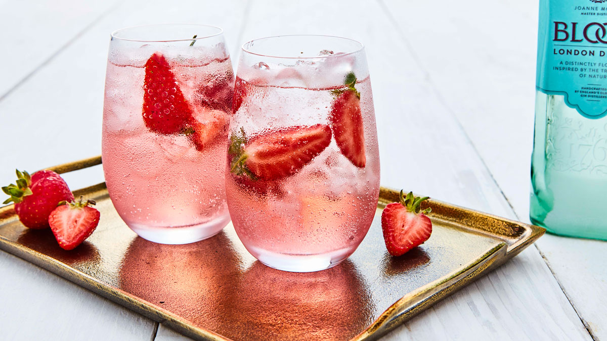 Gin in Full Bloom served in two glasses with ice and sliced strawberries