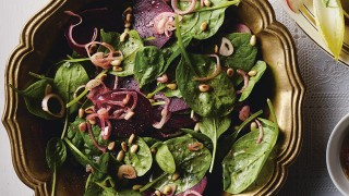 Spinach, Beetroot and Shallot Salad served in an olive coloured dish topped with toasted pine nuts