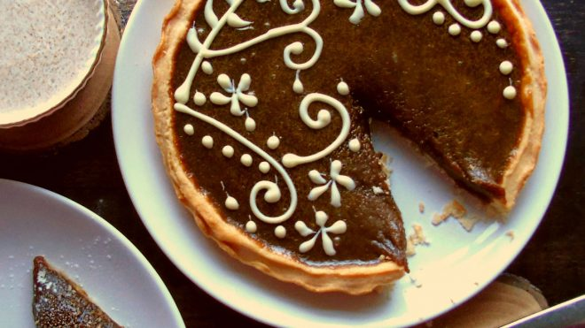 Butterscotch Tart with a Lancaster Honey and Cinnamon Cream served on a white plate with a slice removed