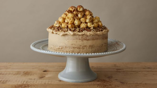 Cappucino Cake topped with popcorn served on a white cake dish