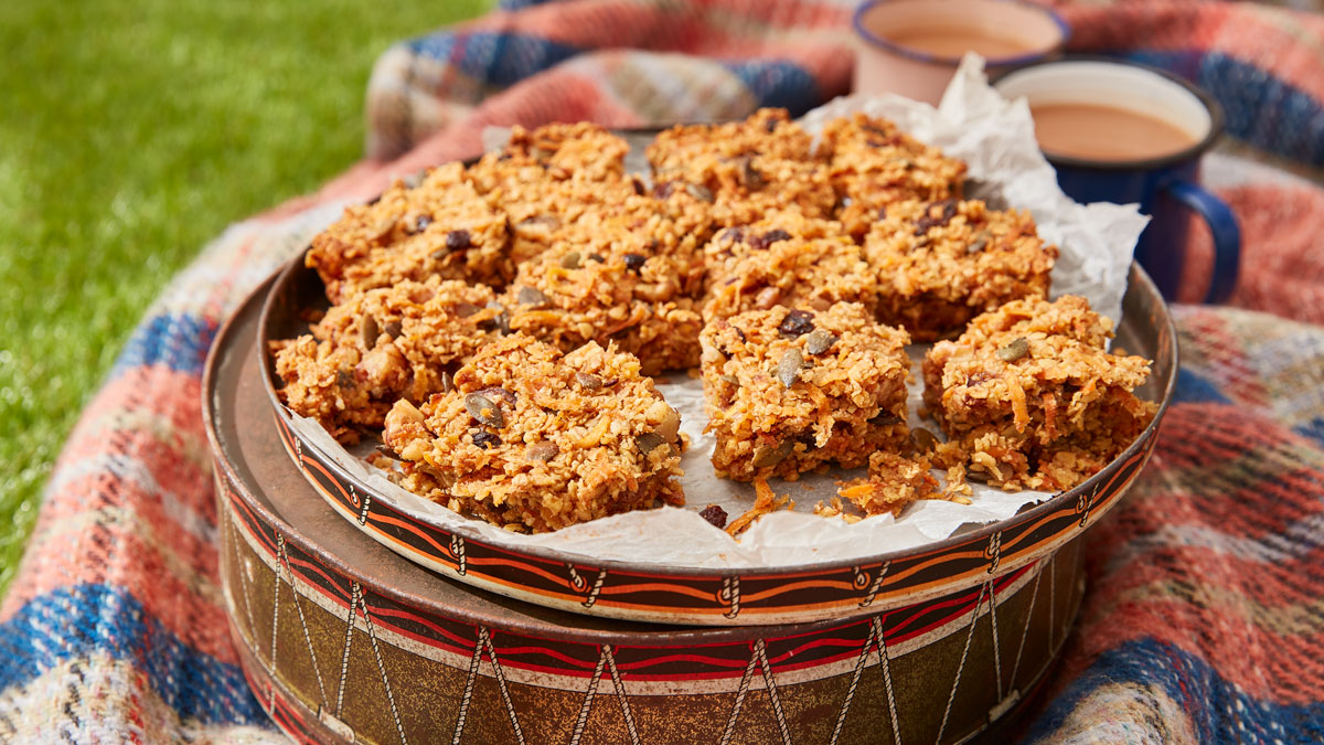 Carrot Cake Flapjack served on top of a cake tin, on a picnic blanket with two cups of tea
