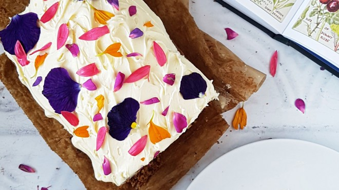 Carrot and Courgette Cake, served on baking parchment and decorated with cream cheese frosting and edible flowers