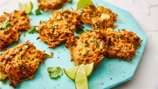 Carrot Fritters served on a blue plate with lime wedges