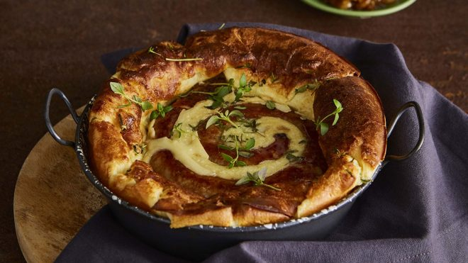 Catherine Wheel Sausage Toad-In-The-Hole served in a casserole dish topped with thyme