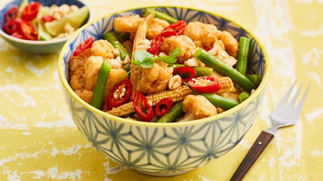 Quick Thai Red Cauliflower Curry served in a patterned bowl topped with fresh red chillies