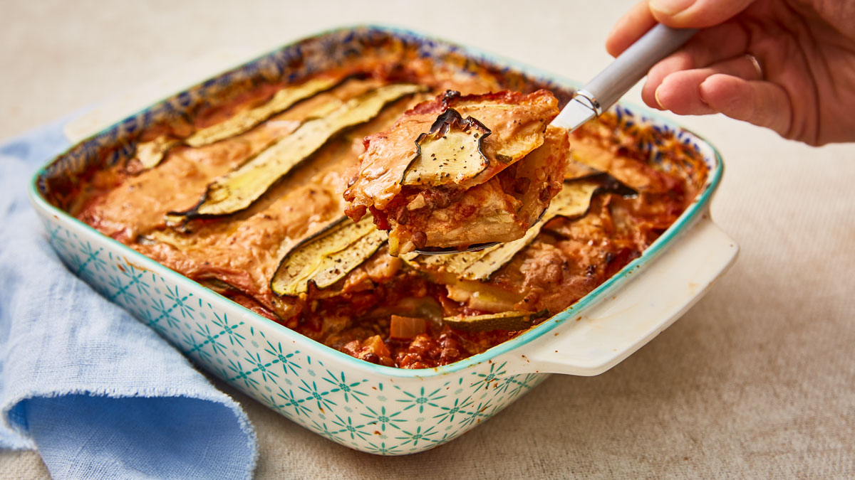 Celeriac, Courgette and Puy Lentil Lasagne served in a casserole dish with a portion being lifted out with a spoon