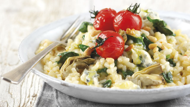 Cheese, Artichoke and Spinach Risotto topped with vine tomatoes and pine nuts served in a white bowl