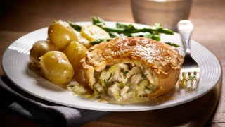Chicken, leek and tarragon pie, served on a white plate with new potatoes and asparagus, with a slice missing to show the filling
