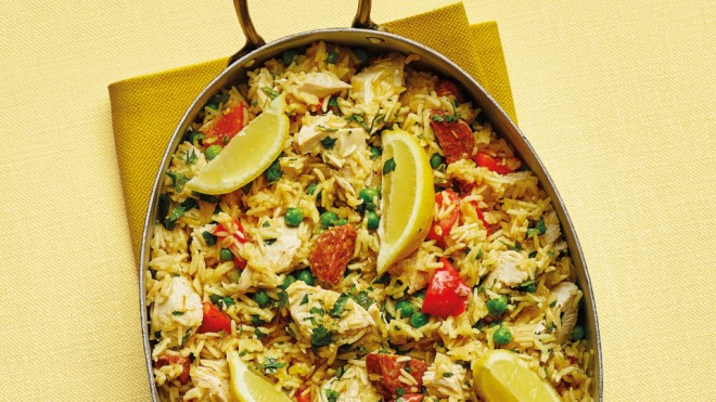 Chicken and chorizo paella served in the pan with lemon wedges on a yellow tablecloth