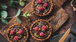 Chocolate and Honey Tarts topped with fresh raspberries and crushed pistachios