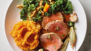 Roast Veal Tenderloin with Sweet Potato Mash, Roast Vegetables and Gravy served on a white plate