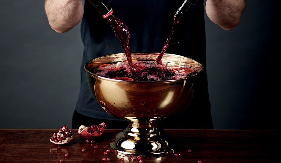Sangria in a golden serving bowl, with red wine being poured in and pomegranates to the side