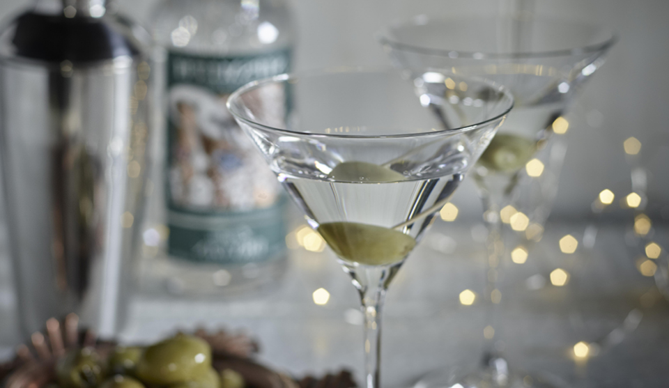 Two Classic Martinis served in glasses with an olive and white fairy lights in the background