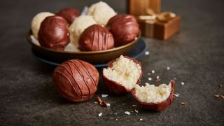 Coconut and Chocolate Truffles served in a gold bowl, with one truffle sliced to see the inside