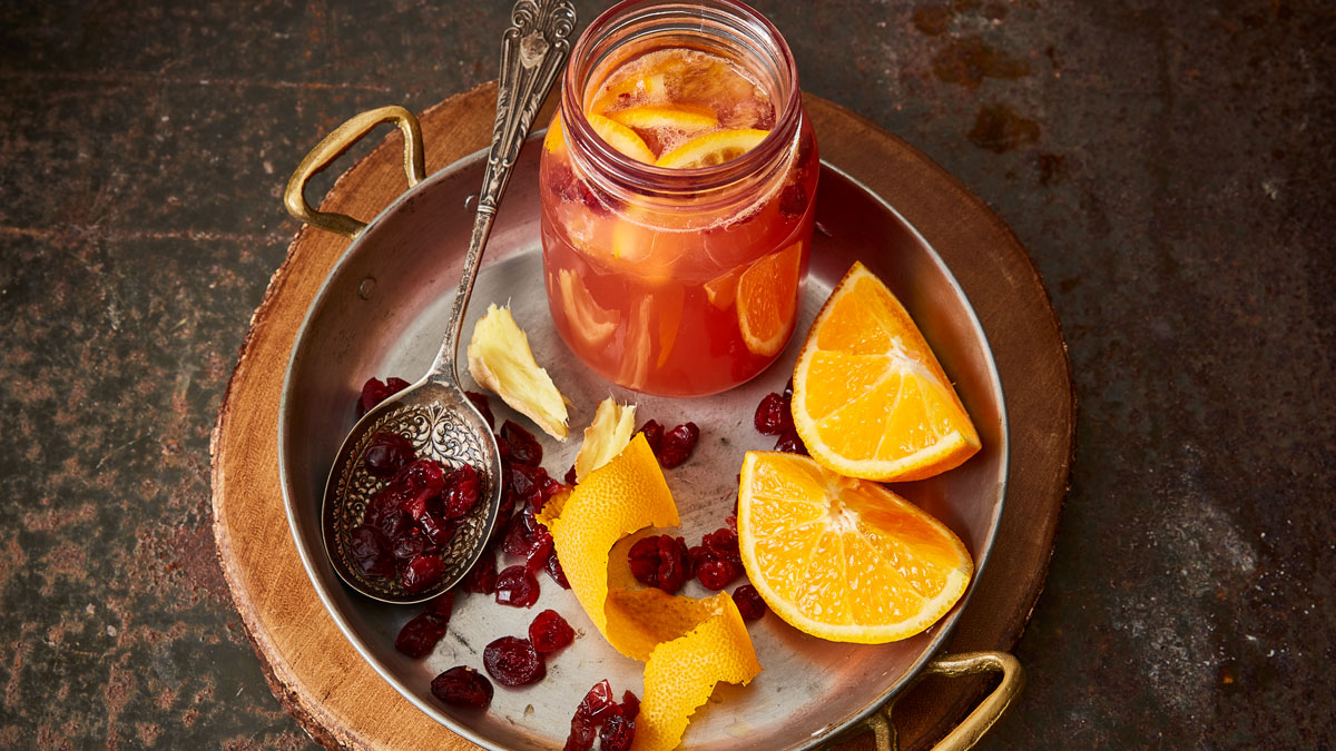Warm Cranberry and Orange Cider Punch served in a glass jar next to sliced oranges