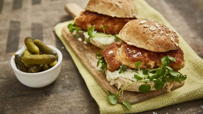 Crispy Fish Burgers served on a wooden board with watercress, next to a bowl of gherkins