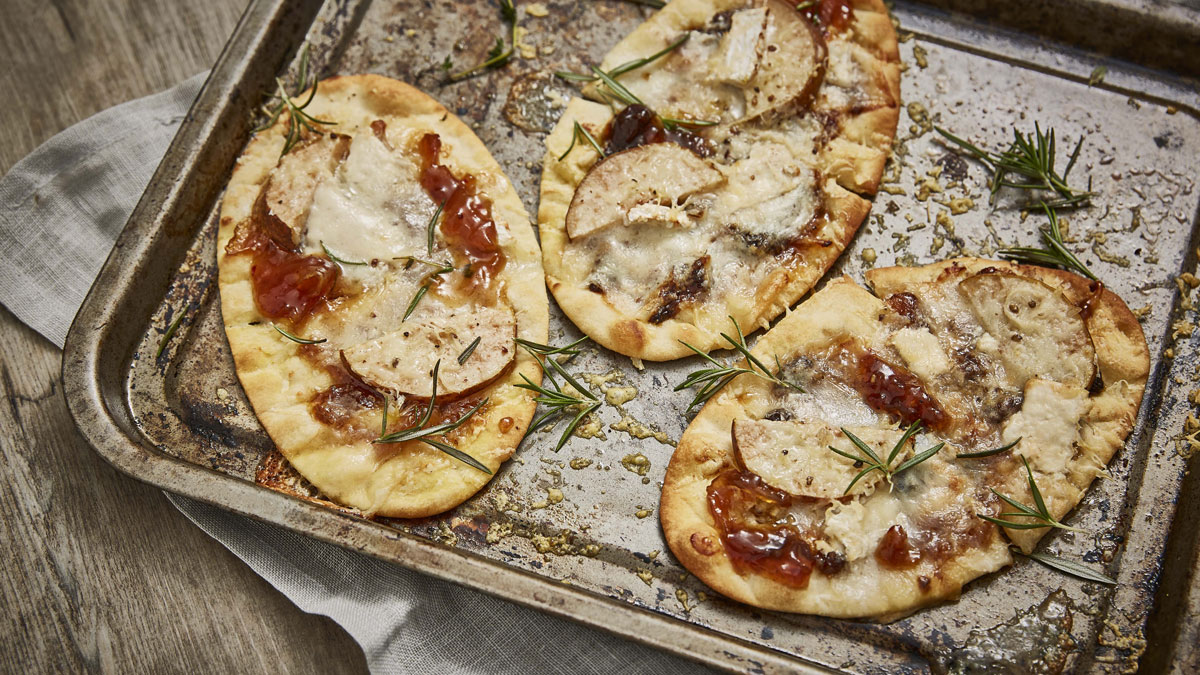 Goats' Cheese, Caramelised Onion and Pear Flatbreads topped with rosemary and served on a baking tray