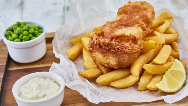 Gluten Free Beer Battered Fish served on top of chips, with a lemon wedge, peas and tartare sauce on baking parchment
