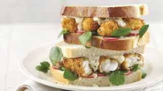 The Ultimate Fish Finger Sandwich served on white bread with watercress, with one sandwich half stacked on top of the other