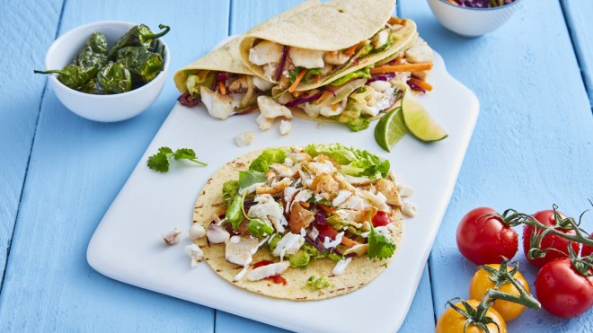 Fish Tacos served on a white board with lemon wedges and coriander