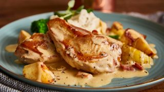 Fricassee of Pheasant, Apples with Cider Crème Sauce served on a blue plate with mashed potatoes and green veg