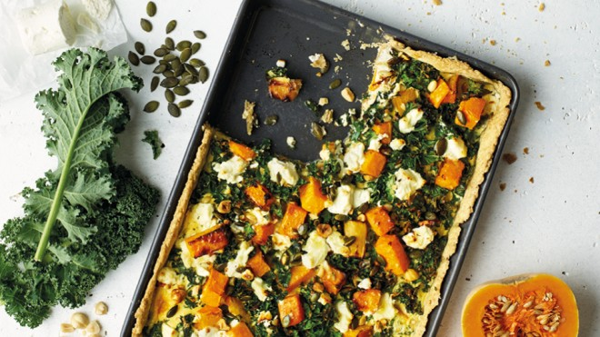 Squash, Kale and Goats Cheese Tart served in a baking grey with a portion removed