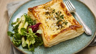 Goats' Cheese, Potato and Thyme Tart served on a blue plate with a side salad