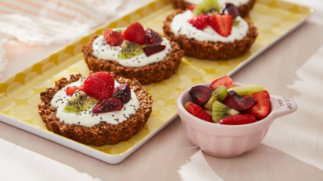 Granola Breakfast Tarts served on a yellow tray next to a bowl of fruit
