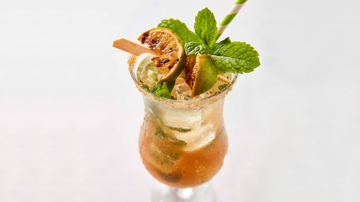 Grilled Mojito Mocktail served in a tall glass with grilled lime wedges and fresh mint