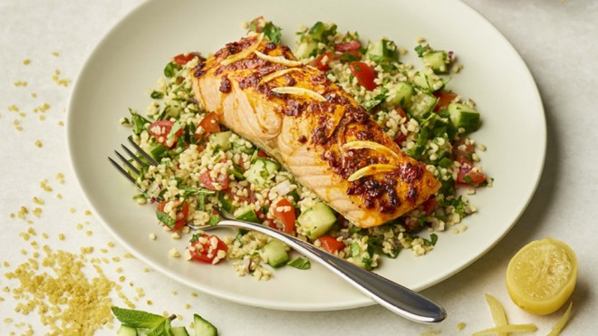 Harissa Salmon with Herby Tabbouleh served on a white plate with a lemon wedge on the side