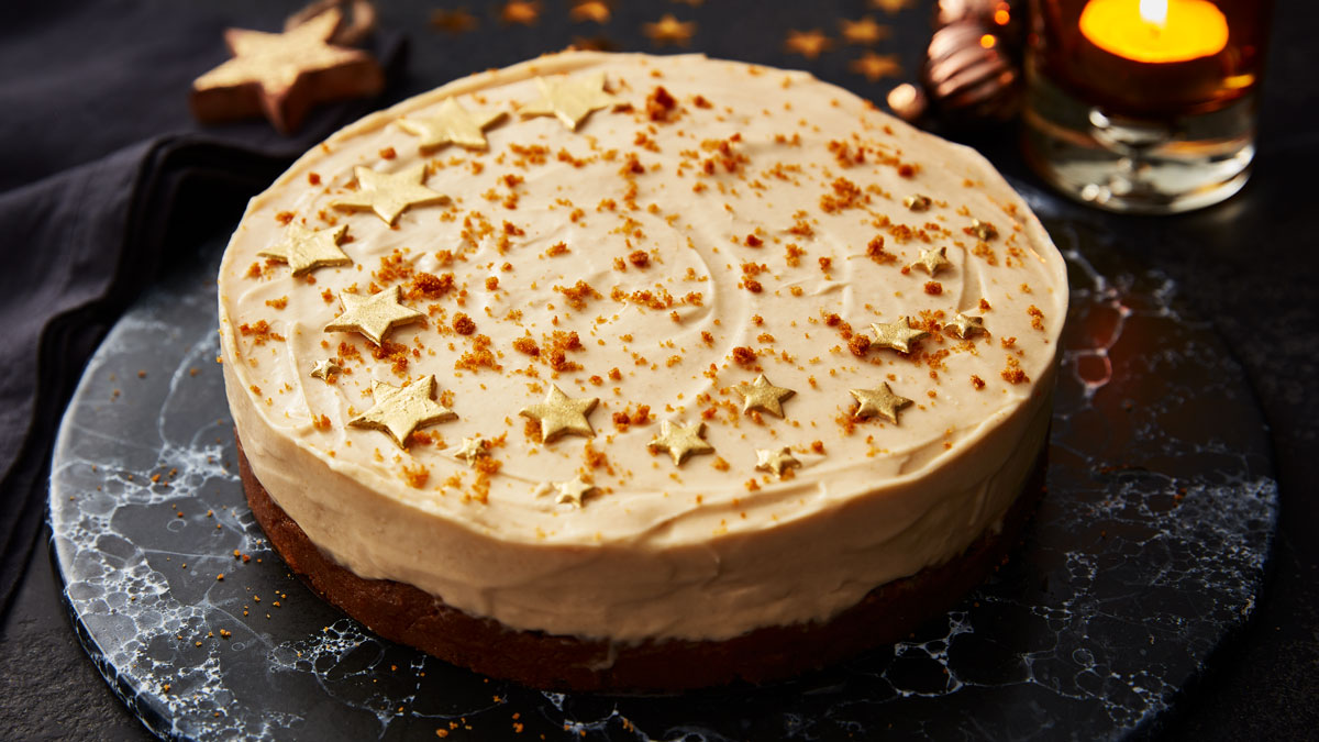Gingerbread Cheesecake decorated with crumbs and gold stars served on a black marble plate