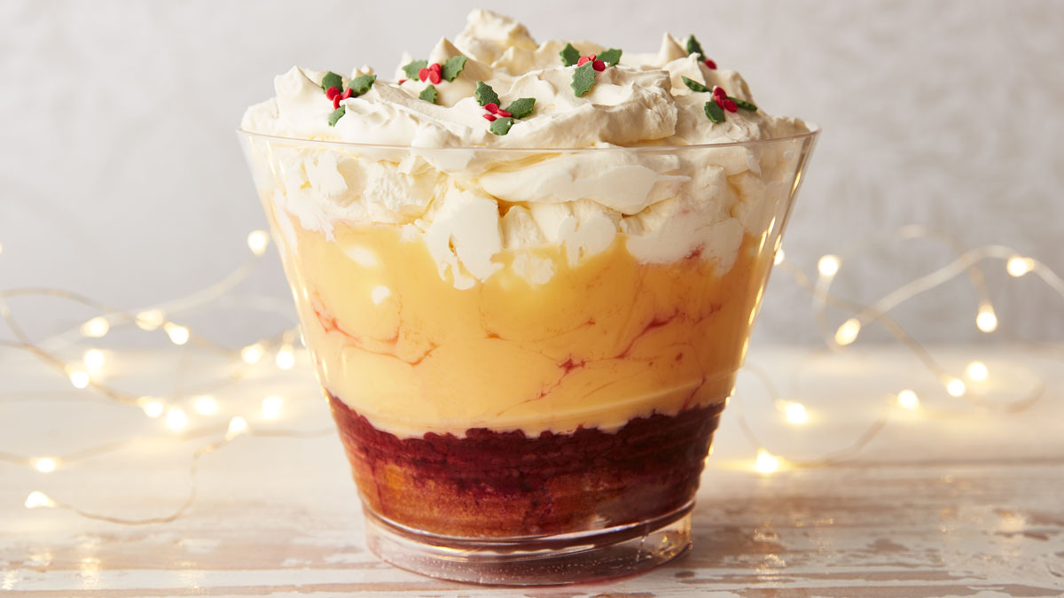 Super Simple TastyTrifle served in a glass bowl, topped with sweet holly leaves with lights in the background