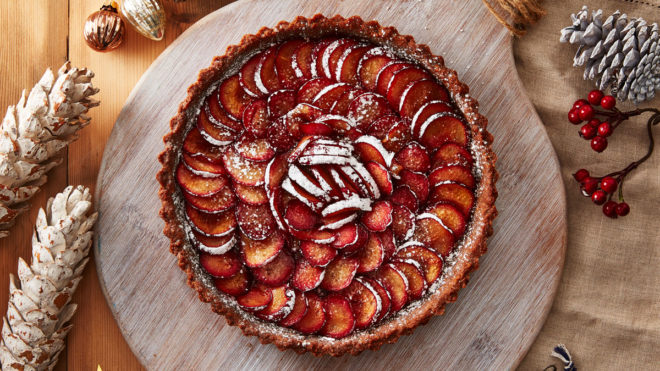 Spiced Plum Tart with Gingerbread Crust served on a wooden board and dusted with icing sugar