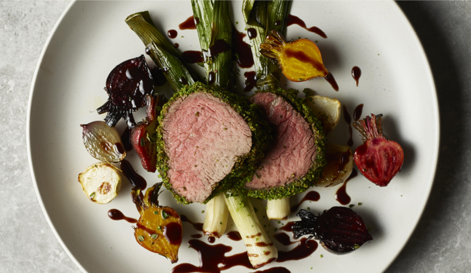 Herb Crusted Filled of Beef served on a white plate with roasted beetroot and red wine sauce