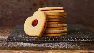 Jammy Love Heart Sandwich Biscuits stacked on top of each other and served on a cooling rack