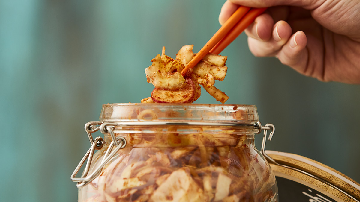 Kimchi being served from a glass jar with chopsticks